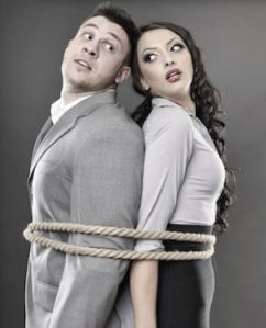 Studio shot of young couple back to back tied with a rope